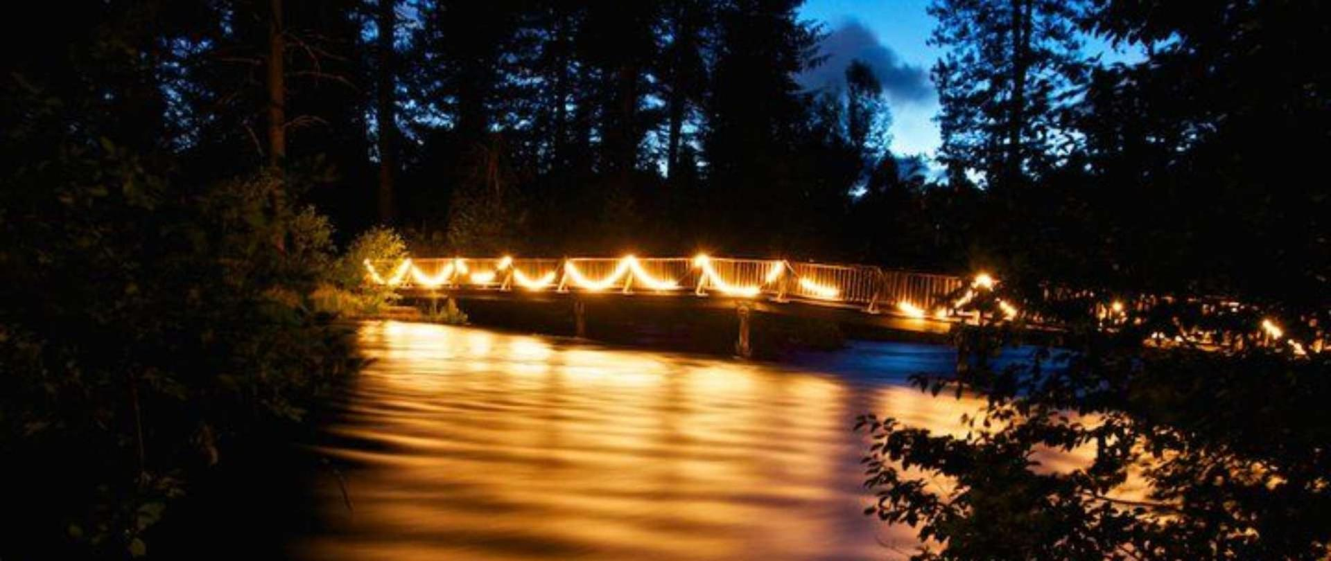 The foot bridge at Cold Springs Resort is beautifully illuminated at night, guiding guests back to their cabins and RVs