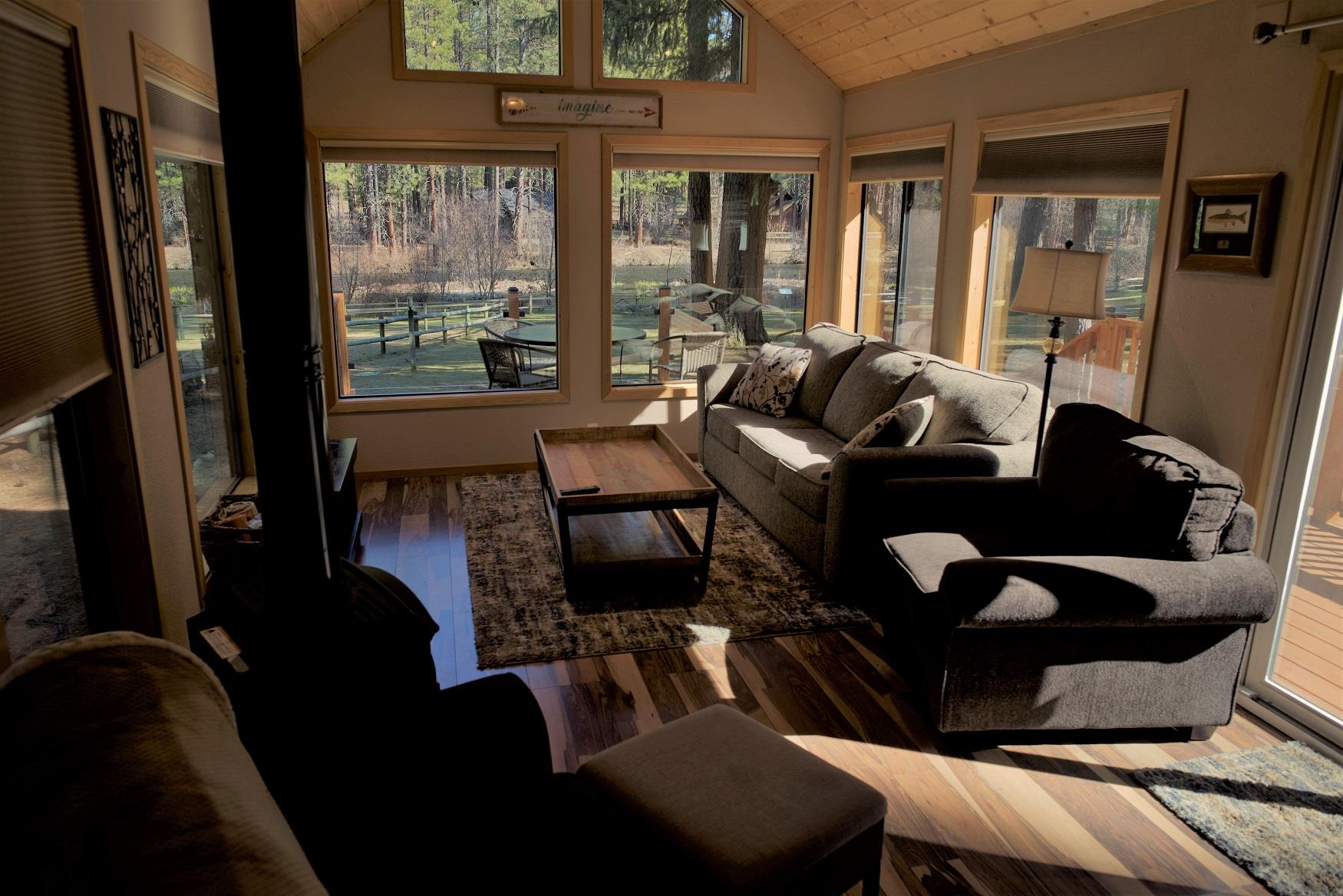 Curl up in front of the fire in the living room of Riverview Cabin, with a perfect view of the Metolius River out the gigantic windows, at Cold Springs Resort and RV Park in Camp Sherman, Oregon