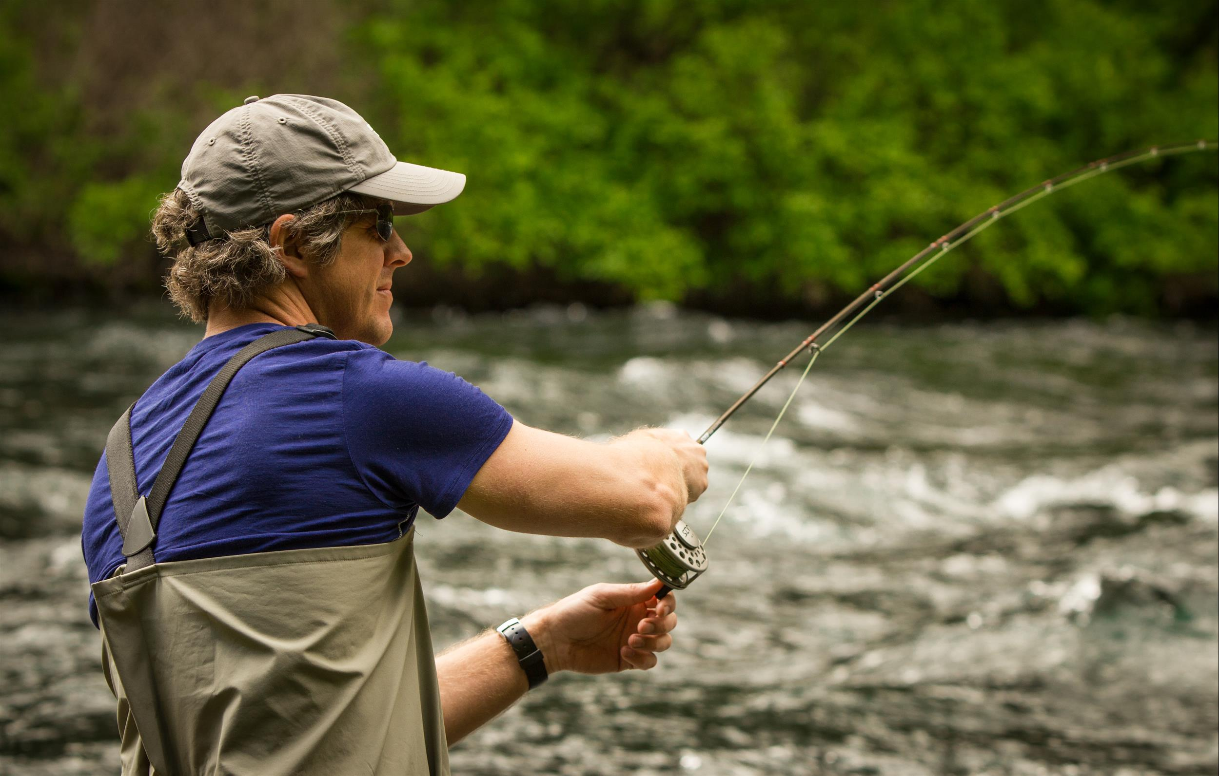Young man fly fishing in the Metolius River at Cold Springs Resort in Camp Sherman, Oregon.